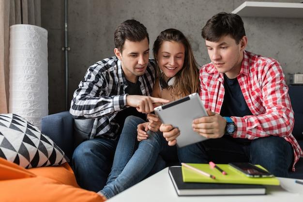 Gelukkige jonge mensen met behulp van tablet, studenten leren, plezier hebben, vriendenfeestje thuis, hipster bedrijf samen, twee mannen een vrouw, glimlachen, positief, online onderwijs