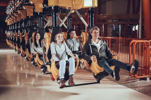 Gelukkige jonge mensen rijden op attracties.