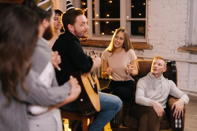 Gelukkige jonge mensen zingen op het nieuwjaarsfeest in een gezellig huis. gelukkig jonge man speelt gitaar.