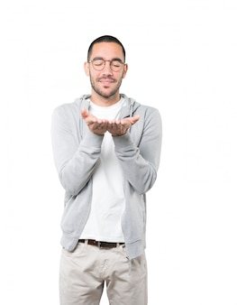 Gelukkige jonge mensenholding iets met zijn hand