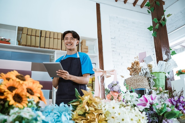Gelukkige jonge mensenondernemer die in bloemenwinkel werkt die schort draagt die terwijl tablet glimlacht