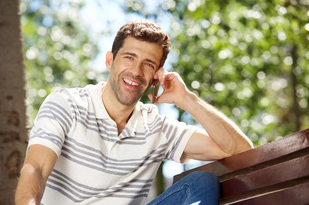 Gelukkige jonge mensenzitting in openlucht en sprekend op celtelefoon