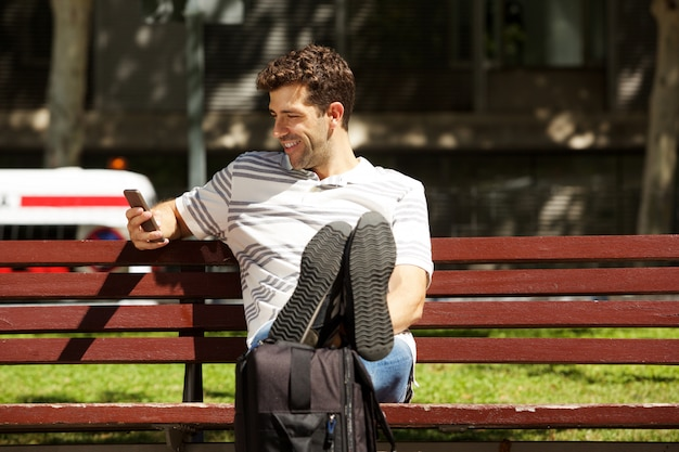 Gelukkige jonge mensenzitting op bank in openlucht met reiszak en mobiele telefoon