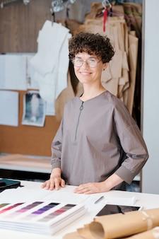 Gelukkige jonge modeontwerper die u per werkplek bekijkt terwijl u textielmonsters uit de catalogus kiest