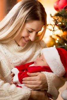 Gelukkige jonge moeder die babyjongen in kerstmankostuum omhelst bij open haard