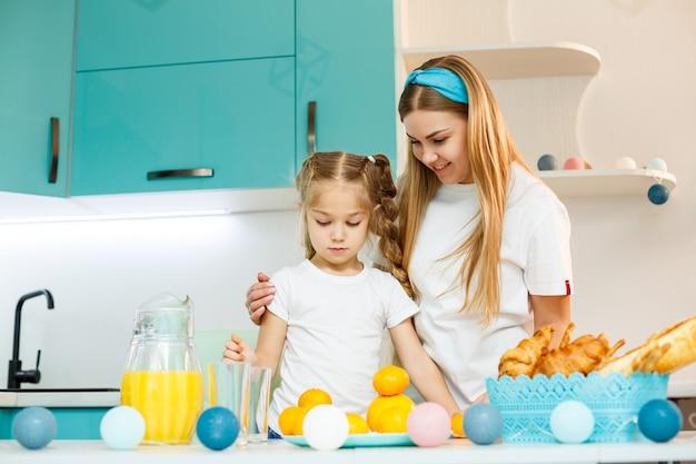 Gelukkige jonge moeder die croissant voor haar dochter in de keuken thuis bakt. gelukkige familierelaties