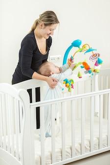 Gelukkige jonge moeder die een schattige babyjongen vasthoudt die in een wit houten bed staat