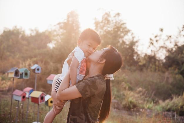 Gelukkige jonge moeder die en pret met haar spelen weinig babyzoon in het park op een zonnige de zomerdag