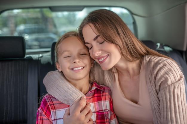 Gelukkige jonge moeder die haar dochter omhelst, wang aan wang zit op achterbank van auto