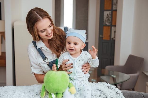 Gelukkige jonge moeder die haar zoontje met speelgoed thuis vasthoudt en speelt