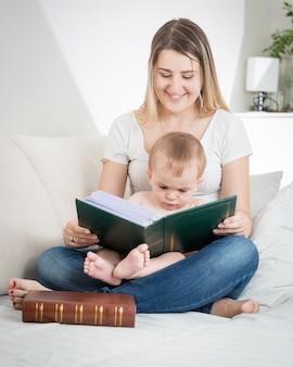 Gelukkige jonge moeder die op de bank in de woonkamer zit en een boek leest voor haar babyjongen