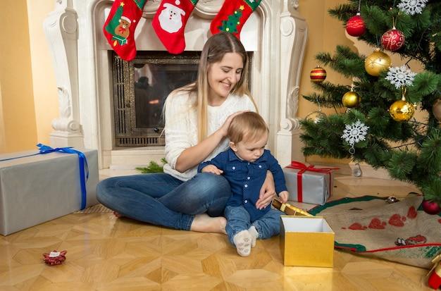 Gelukkige jonge moeder die op de vloer zit met zoontje in de woonkamer, versierd voor kerstmis