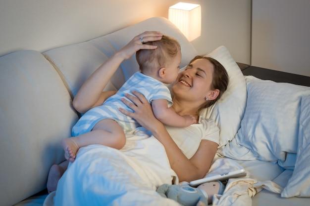 Gelukkige jonge moeder die 's avonds laat haar babyjongen in bed speelt en omhelst