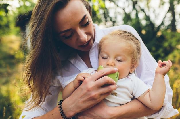 Gelukkige jonge moeder en de mooie appel van de dochterholding