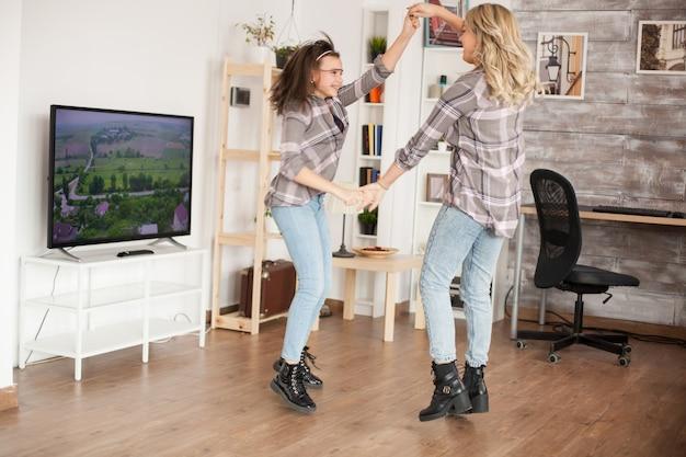 Gelukkige jonge moeder en dochter springen rond in de woonkamer. mooie jeugd.