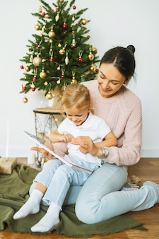 Gelukkige jonge moeder en dochtertje kijken naar een familiealbum of lezen een boek terwijl ze onder de kerstboom zitten