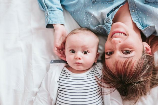 Gelukkige jonge moeder en haar babyjongen die bij bed en het glimlachen liggen