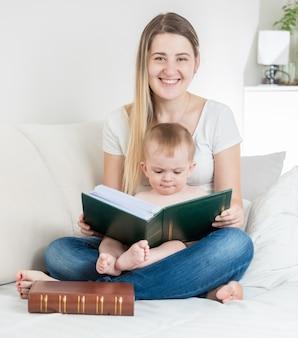 Gelukkige jonge moeder en haar babyjongen poseren met een groot boek