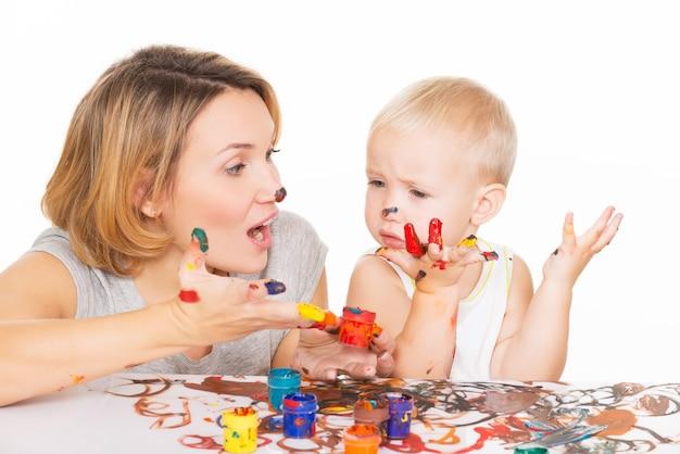 Gelukkige jonge moeder en kind met geschilderde handen die op wit worden geïsoleerd.