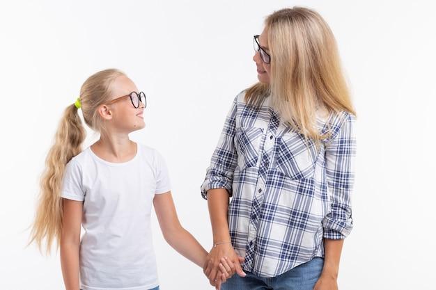Gelukkige jonge moeder en lachend kind in mode-bril hebben plezier op witte achtergrond