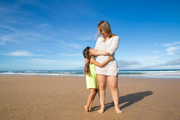 Gelukkige jonge moeder en schattig zwartharig meisje knuffelen terwijl staande op oceaan strand
