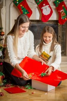 Gelukkige jonge moeder en schattige dochter die kerstcadeaus in rood papier inpakken en vastbinden met gouden lint