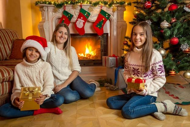 Gelukkige jonge moeder en twee dochters zitten met kerstcadeaus op de vloer naast een brandende open haard