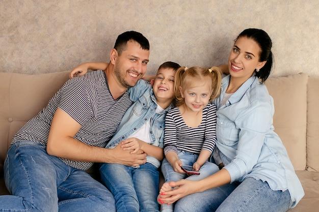 Gelukkige jonge moeder en vader met twee kinderen die op de bank zitten, elkaar bekijken, geniet het gezin van een teder moment. communiceert online met familie en vrienden.