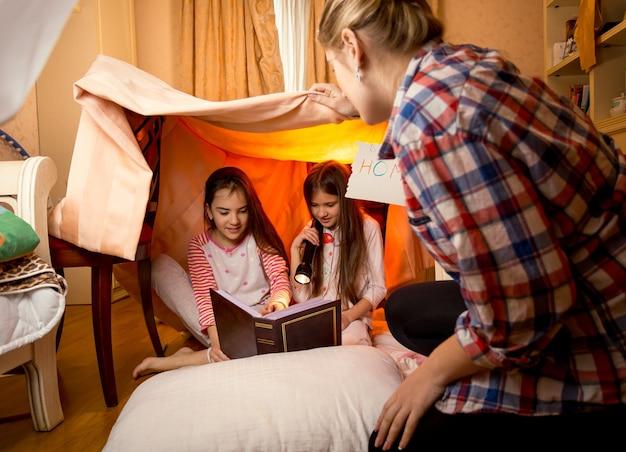 Gelukkige jonge moeder kijkt naar twee dochters die een boek lezen op de vloer in de slaapkamer