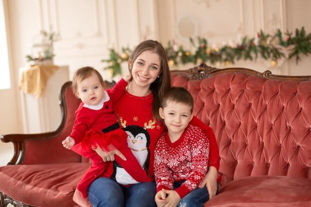 Gelukkige jonge moeder koestert haar zonen op de bank in de buurt van de kerstboom