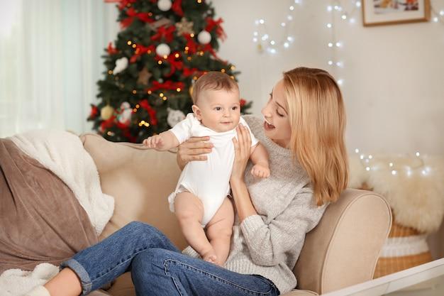 Gelukkige jonge moeder met baby in versierde kamer voor kerstmis