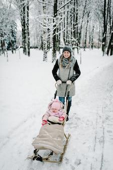 Gelukkige jonge moeder met dochter, wandelingen met baby en een kinderslee buiten op de achtergrond winter.