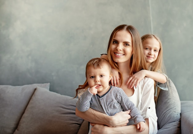 Gelukkige jonge moeder met haar kinderen hebben plezier thuis