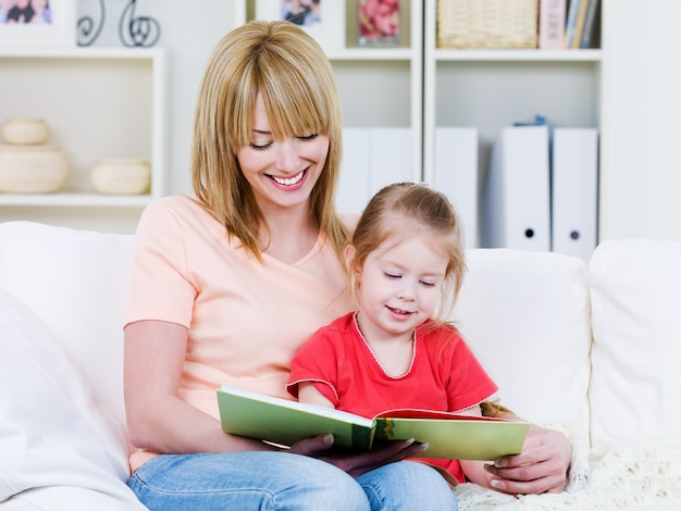 Gelukkige jonge moeder met haar kleine glimlachende dochter die bood samen - binnen leest