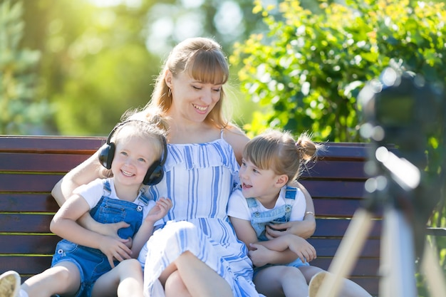 Gelukkige jonge moeder met kinderen voor een videocamera.