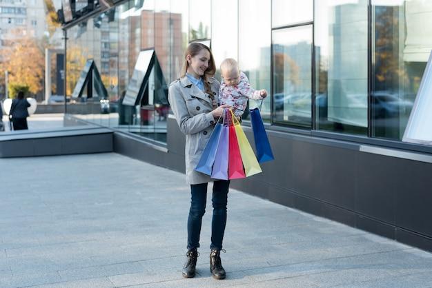 Gelukkige jonge moeder met kleine dochter op de armen en boodschappentassen in de hand. shop dag. winkelcentrum
