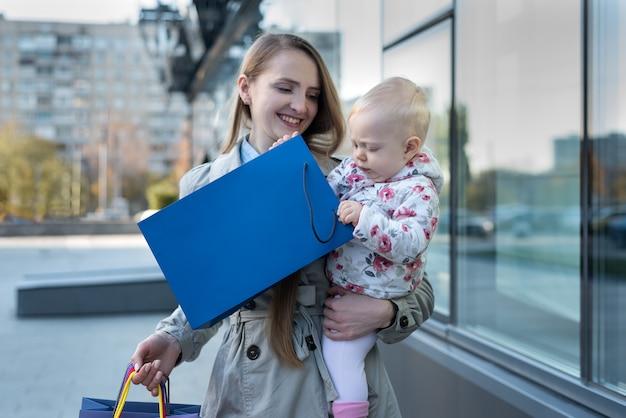 Gelukkige jonge moeder met kleine dochter op de armen en boodschappentassen in de hand. shop dag.