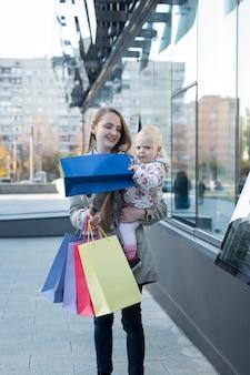 Gelukkige jonge moeder met kleine dochter op de armen en boodschappentassen in de hand,