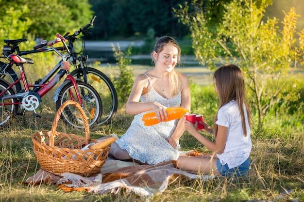 Gelukkige jonge moeder met picknick aan de rivier met dochter. moeder giet sinaasappelsap in de beker van de dochter