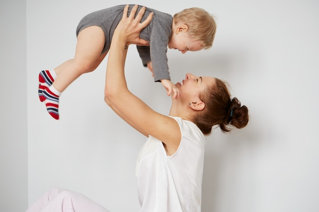 Gelukkige jonge moeder met zoontje thuis