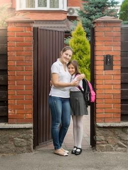 Gelukkige jonge moeder staat met haar dochter in schooluniform in de achtertuin van het huis