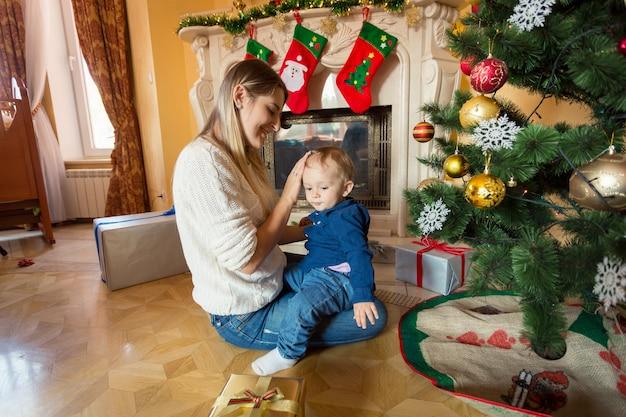 Gelukkige jonge moeder zit met haar babyjongen op de vloer bij de kerstboom
