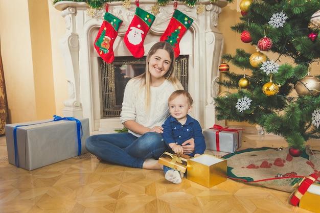 Gelukkige jonge moeder zit met haar zoontje op de vloer in de woonkamer naast de open haard en de kerstboom