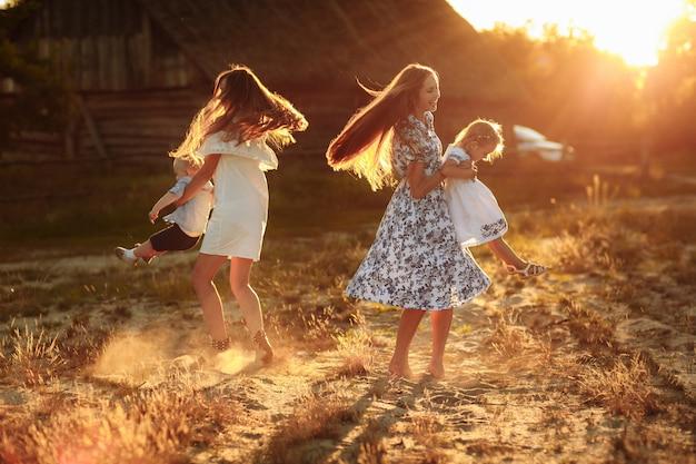 Gelukkige jonge moeders die met hun jonge geitjes in openlucht spelen