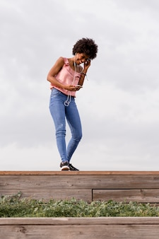 Gelukkige jonge mooie afro amerikaanse vrouw die en op haar mobiele telefoon glimlacht spreekt. bewolkte achtergrond. lente of zomer seizoen. casual kleding
