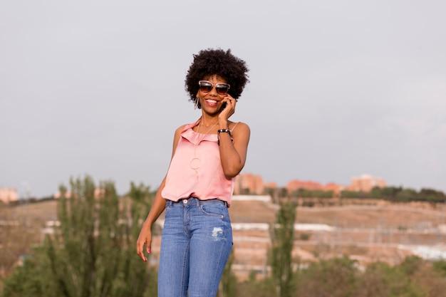 Gelukkige jonge mooie afro amerikaanse vrouw die en op haar mobiele telefoon glimlacht spreekt. stedelijke achtergrond. lente of zomer seizoen. casual kleding