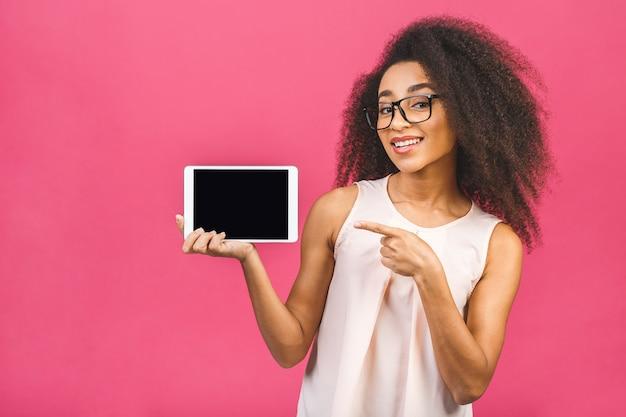Gelukkige jonge mooie afro amerikaanse vrouw die lege tabletcomputer over roze toont. wijzende vinger.