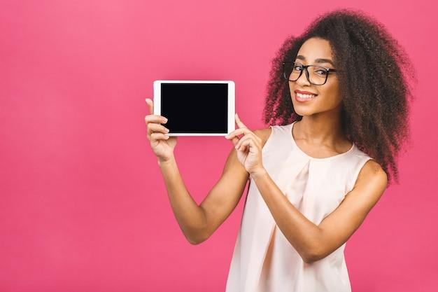 Gelukkige jonge mooie afro amerikaanse vrouw die lege tabletcomputer over roze toont.
