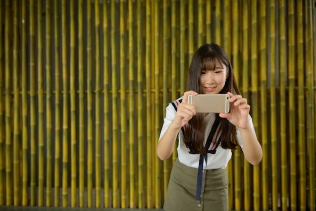 Gelukkige jonge mooie aziatische tiener die foto met telefoon tegen bamboeomheining neemt
