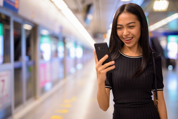 Gelukkige jonge mooie aziatische toeristenvrouw die telefoon met behulp van bij het metrostation